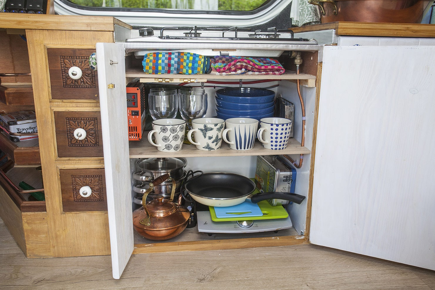 A well stocked cupboard with all you need, plates, cups, glasses, ons and induction hob.