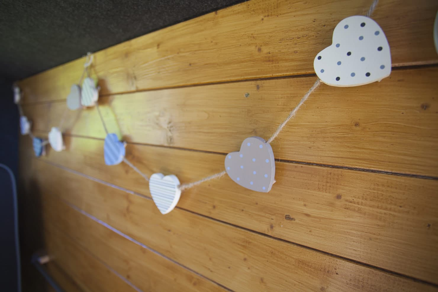 Showing the Love with hearts on a string over a rustic wood panelled wall inside the campervan
